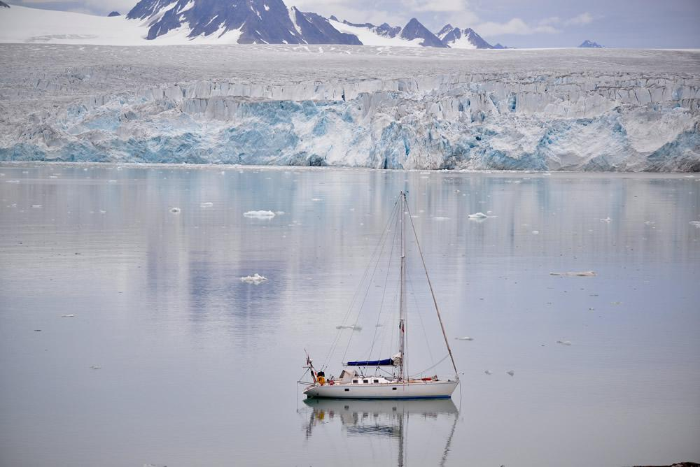 Sailboat at anchor in front of glaciers